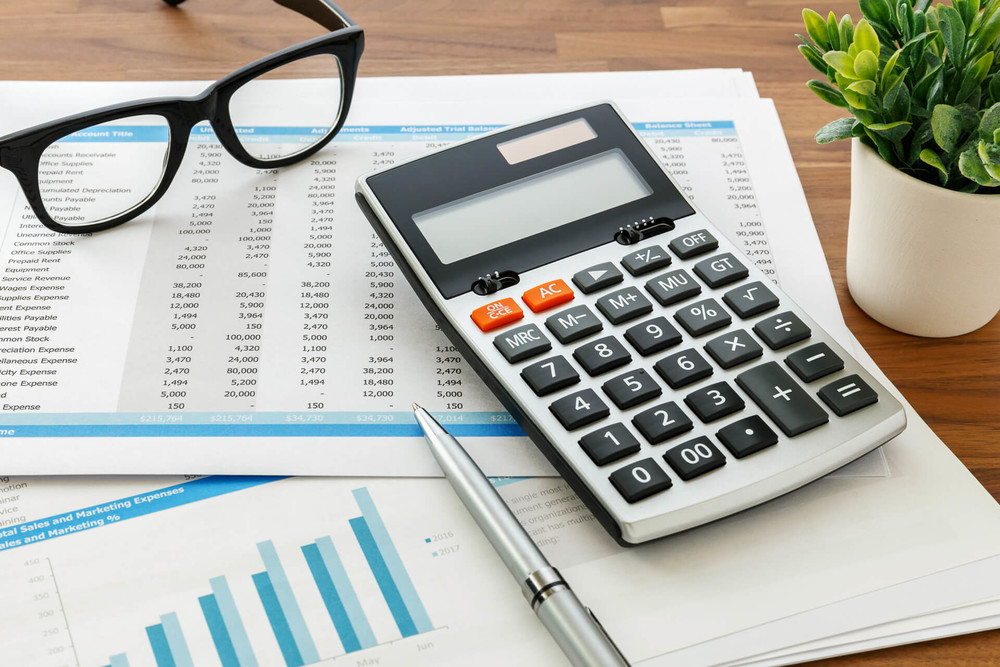 Calculator and glasses can help when you calculating your investment property profit or loss