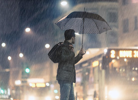 Man holding umbrella covered with income protection insurance