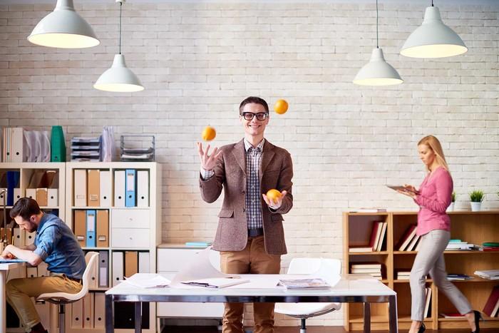 Man juggling oranges to demonstrate multitasking