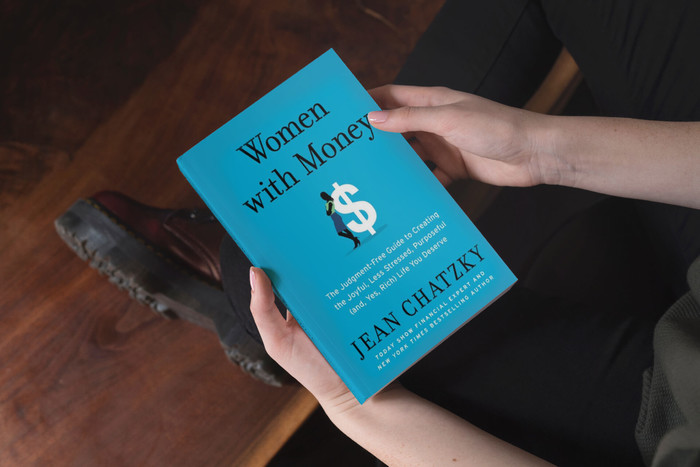 A person holding the book Women with Money in their arms while sitting