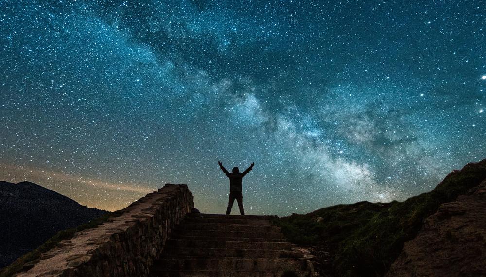 Man standing in the desert raising his hands towards the Milky Way galaxy