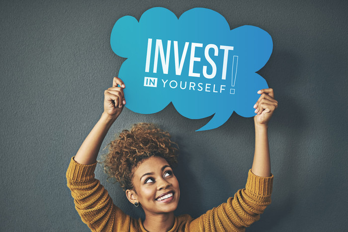 Woman holding a sign which states: invest in yourself