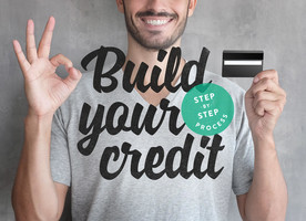 Man smiling holding a credit card