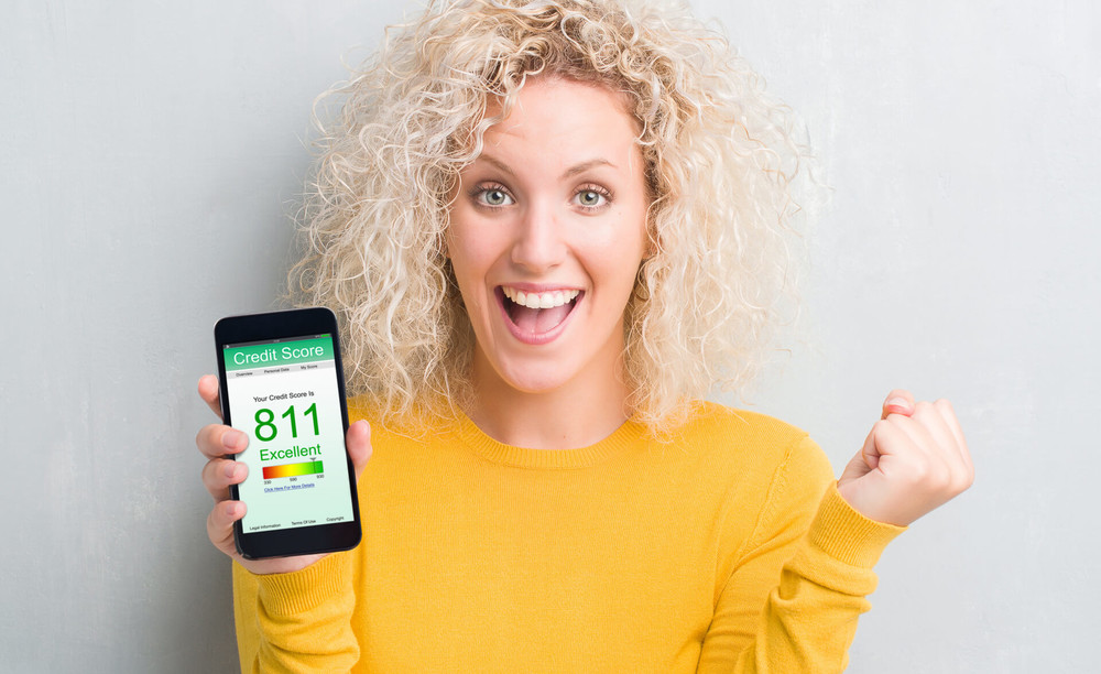 woman shows high credit score on her mobile phone