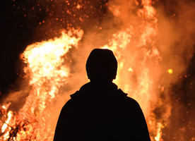 Silhouette man wearing a jacket and hat staring at a fire