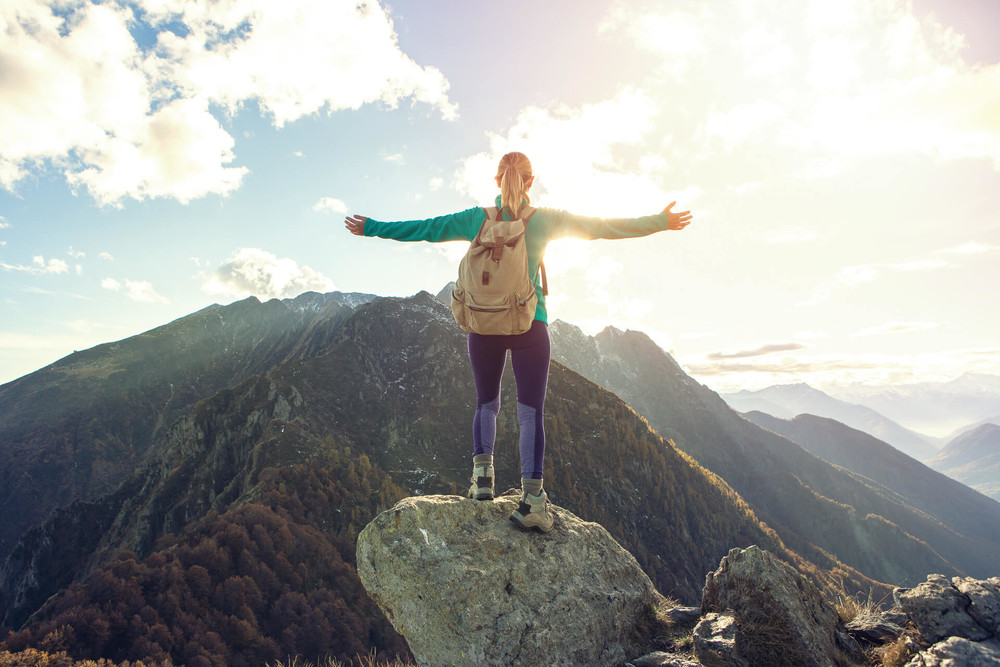 Woman at the top of the mountain shows the results of goal setting