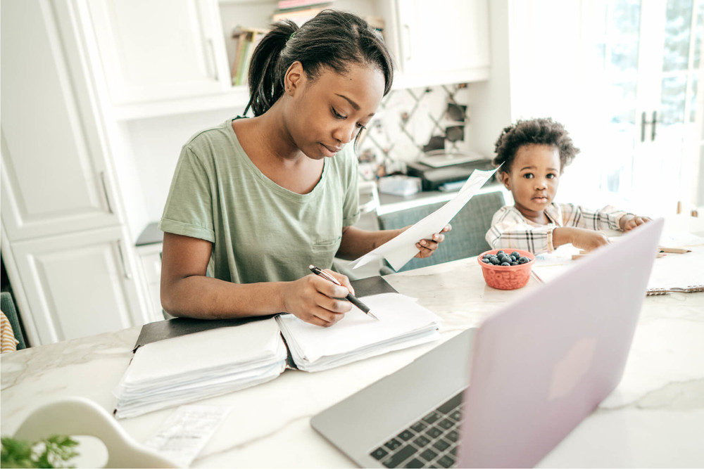 Woman working on her taxes with her son from her home