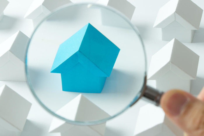 Real estate property under magnifying glass